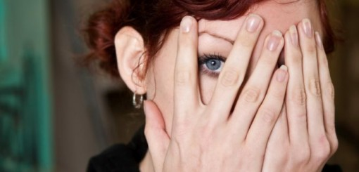 Woman peeking between fingers as she holds her hands in front of her face