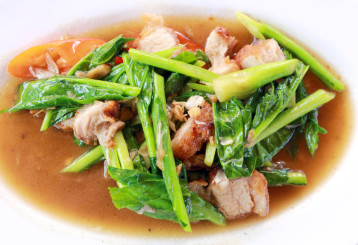 Bowl of crispy pork stir-fry with kale