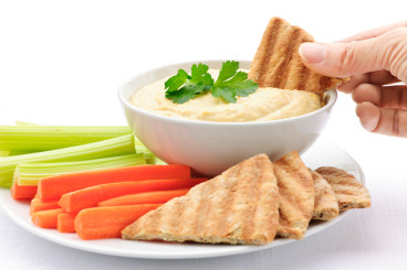 Photo of a hand dipping pita in hummus