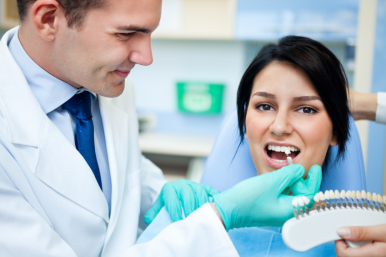 Dentist examining a whiteness of teeth of a patient