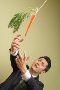 man in suit lunging for a carrot on a string