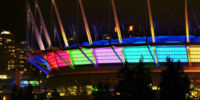 BC place stadium lit up at night with rainbow colours