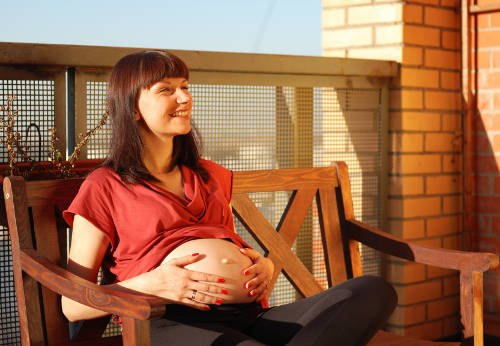 smiling pregnant woman on bench